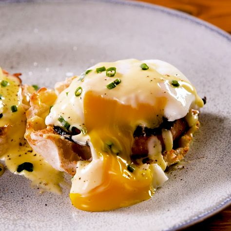 Eggs Benedict is a traditional breakfast dish composed of an English muffin topped with Canadian ham, poached eggs, and hollandaise sauce. Get the recipe at Delish.com. #delish #easy #recipe #eggs #benedict #eggsbenedict #poachedeggs #bacon #englishmuffins #breakfast #brunch #lemonjuice