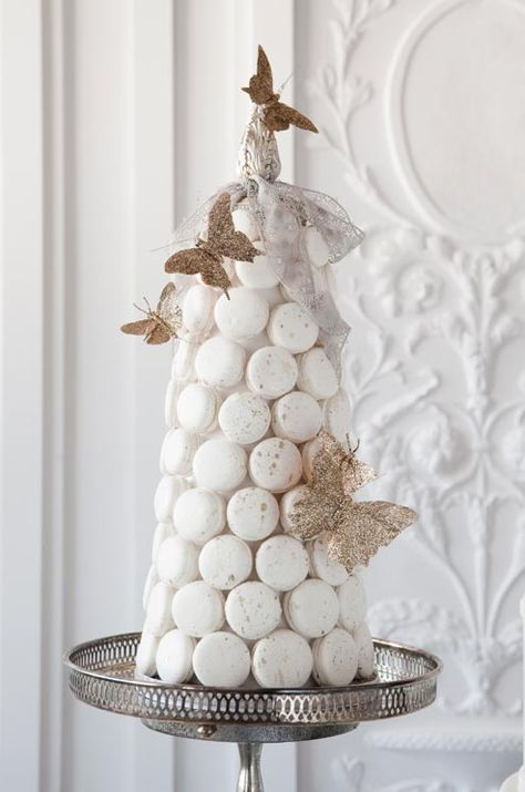 Hand-sculpted butterflies perch precariously on a tower of white macarons, but I would like teal and purple macarons with butterflies made out of peacock feathers :)