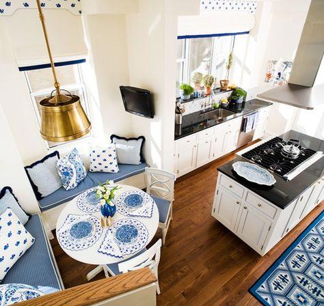 elegante sitzecke küche in weiß mit weißem Esstisch rund und blauen kissen und tisch set