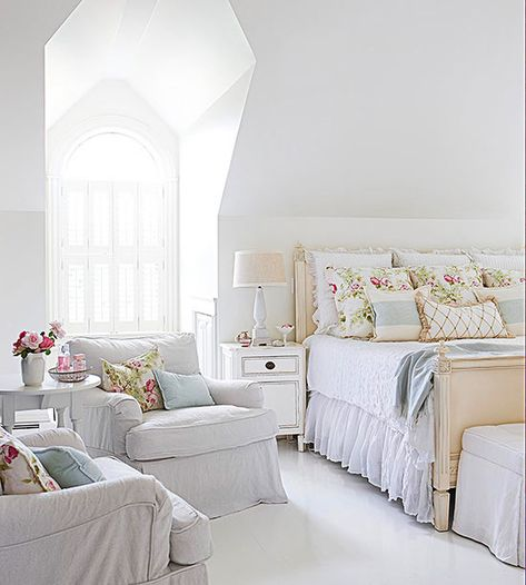 In an almost all-white room, hints of pale blue and pink go a long way to add feminine flair to the angular lines of this bedroom. A flirty bed skirt and flowy slipcovers on the armchairs and ottoman also soften the look, as
