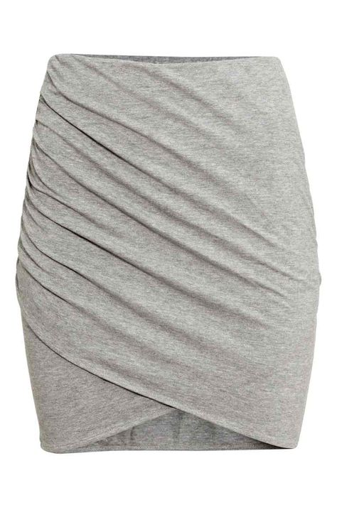 Short skirt in jersey with attached, draped front wrap section.