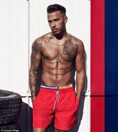 Lewis Hamilton goes shirtless showing off his tattoos in a Tommy Hilfiger image.