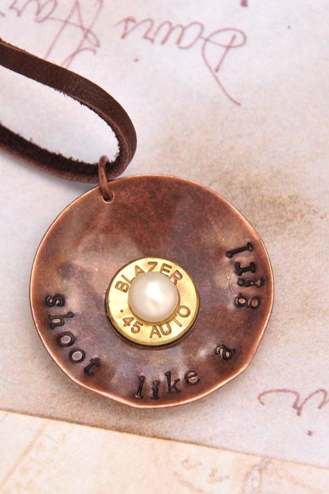 An antique copper circle (1 1/4 inch) has been hand stamped with shoot like a girl. The disc has been lightly hammered until it is slightly