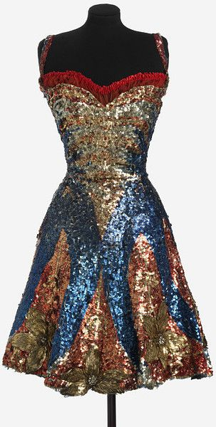 Theater costume for music-hall performer May Moore Duprez circa 1910.  Materials: Sequins and net on a cotton backing.  Every millimeter is encrusted with sequins, each one painstakingly sewn on by hand, and the costume would have shone and sparkled under the stage lights. As she moved the skirt, Duprez's legs would have been revealed surrounded by a froth of underskirts in the finest chiffon, which would also have helped cushion her legs against the weight of the sequined skirt.