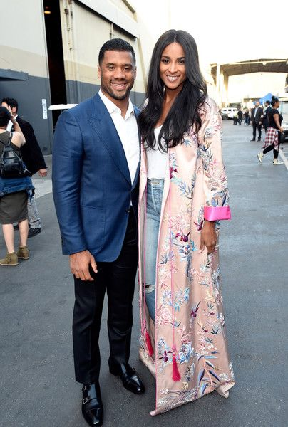 NFL player Russell Wilson and singer Ciara pose backstage during 'One Voice: Somos Live! A Concert For Disaster Relief.'