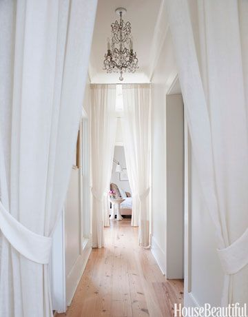 Designer Smith Hanes turned a negative in the home into a fresh, beautiful positive: he broke up the long hallway leading to the master suite by adding a row of white portieres.