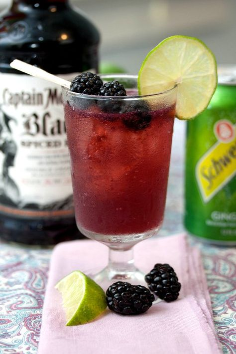 Blackberry Cream Soda - 1.5 ounces Captain Morgan Spiced Rum, 3 ounces ginger ale, 1 tsp blackberry puree, 1 lime, juiced, lime wedges, ice