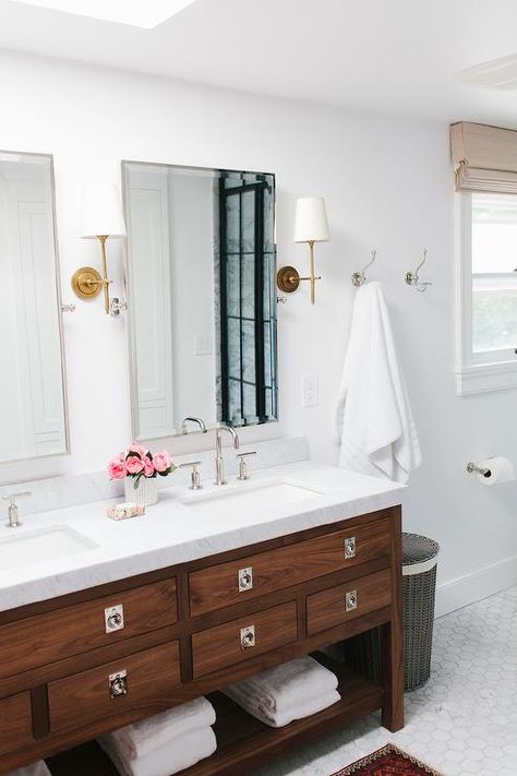 Gorgeous bathroom boasts a freestanding walnut dual vanity with shelf adorned with chrome hardware topped with white marble fitted with his and hers sinks and Kohler Purists Faucets under Restoration Hardware Lugarno Traditional Pivot Mirror illuminated by Thomas O'Brien Bryant Sconces in Hand Rubbed Antique Brass.