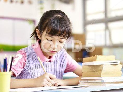 Asian schoolgirl studying in classroom ~ Premium Photo #86418814