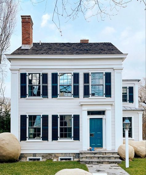 This charming colonial home with white clapboard siding and a blue solid front door. The little lampost outside the reont step is great too.