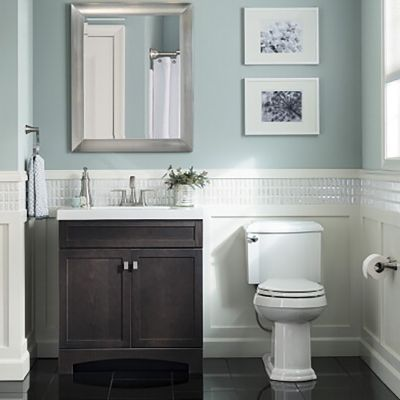 A 30 Inch Brown Drayden Vanity Beside A White Toilet In A Bathroom With Tranquil Blue Walls 249 Bathroom Wall Colors Wainscoting Bathroom Small Bathroom