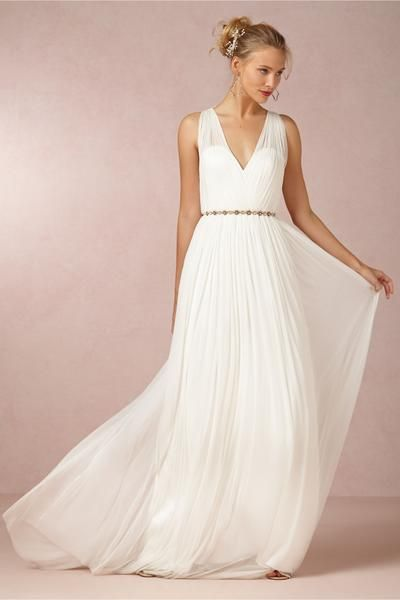 The Ruth gown is made from a silk, tulle a- sheer fabric for a light and airy look and feel. The softness of this gown gives the perfect draped look and light feel. The wide straps and plunging neckline reveal a sexy shoulder and sophisticated bodice, while the open back and skinny, gold flowered belt complete this wedding day look.