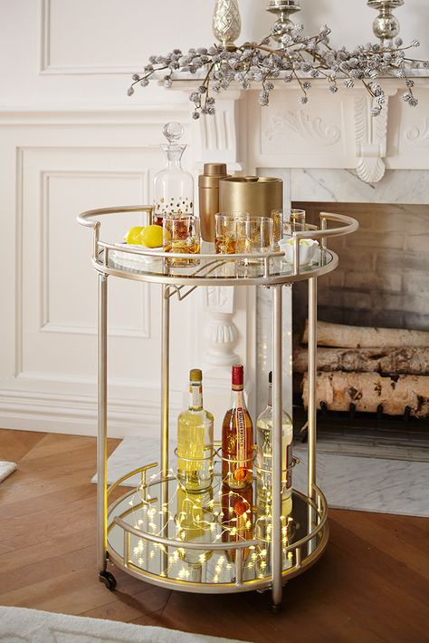 """Pop open a bottle of bubbly and toast the new year with plenty of shimmer and shine. We've raised the bar for at-home entertaining with our Round 2-Tier Bar Cart. Crafted of wrought iron with a champagne finish, our stylish cart boasts a top shelf of tempered glass and a lower shelf with a mirrored surface and three bottle rings to store your favorite libations. A rack attached to the top shelf conveniently stores stemware. Exclusively Pier 1 Imports. #""""barcartideas"""""""