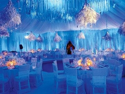 With white draping and light blue lighting, this ballroom appears ...