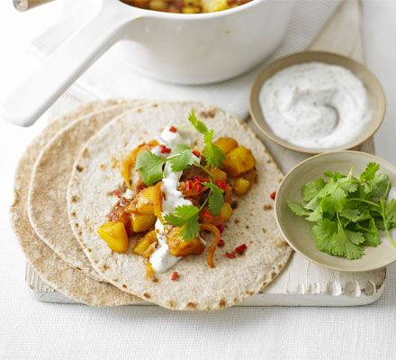Mumbai potato wraps with minted yogurt relish.  - sunflower oil.  - 1 onion.  - 2tbsp medium curry powder.  - 400g chopped tomatoes.  - 750g potatoes.  - 2 tbsp spiced mango chutney.  - 100g low-fat natural yogurt  - 1 tsp mint sauce  - plain chapatis  - coriander sprigs