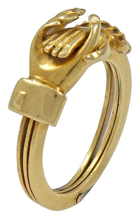 An Early Victorian Gold Clasped Hands Betrothal Ring. The Clasped Hands, which have a male and female cuff, open to reveal a Gold Heart on the central band. Circa 1840