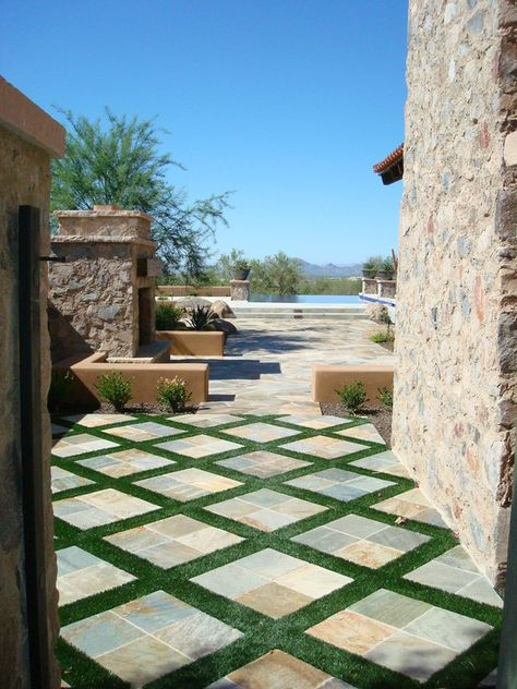 Use fake grass in between tiles in courtyard makes this look work.  You don't have to worry about how to maintain the grass or what happens if the grass dies...