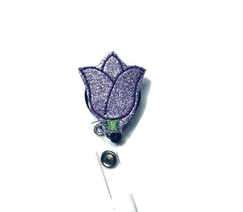~This is a listing for a Purple Tulip Badge Reel, Spring Badge Reel, Glitter Vinyl Badge Reel, Nurse Badge Reel, Teacher Badge Reel, Name Tag Holder, Work Badge Reel ~These are perfect badge holders and we are starting to offer a variety to choose from. ~We attach feltie to your choice of a retractable alligator swivel clip or a slide clip badge reel. Refer to picture above for the different types and make your choice in the drop down. ~All reels come in black. ~Check out the rest of our badge r
