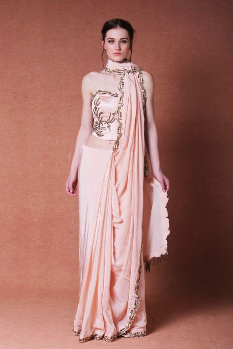 Featuring a peach hand embroidered crepe saree with a satin lycra base corset. Borders of the saree are embroidered with dabka, moti and sequin in a beautiful pattern. It is paired with a tube corset that is embroidered at the neckline and right side waist area. The saree is finished with bugle beads tassels at the pallu. Color: Peach Material: crepe and satin lycra Dry clean only