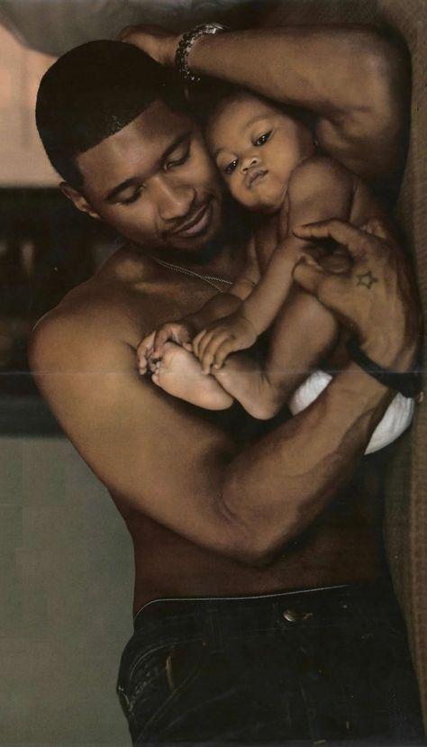 Usher Raymond IV holding his son, Usher Raymond V.
