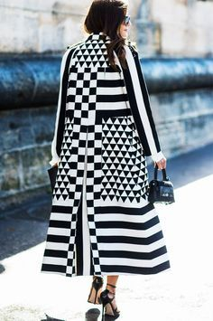 A black and white graphic print coat is paired with a top-handle bag and black strappy sandals