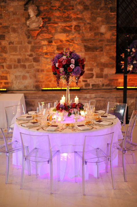 A Wedding Reception Table Takes On Purple Hue When Lit