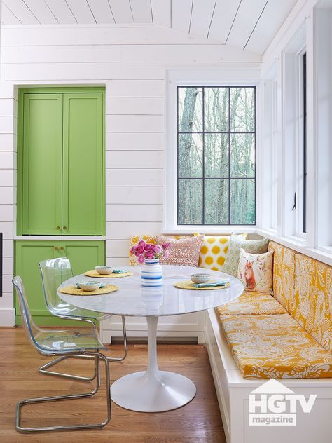 Deep yellow fabrics, bright green paint and modern furniture make this farmhouse style kitchen (complete with white shiplap) shine. See more on HGTV.com.