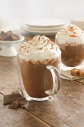 Chocolate caliente  Una rica mezcla de chocolate y leche, decorada con crema batida y un final de mocha espolvoreado.
