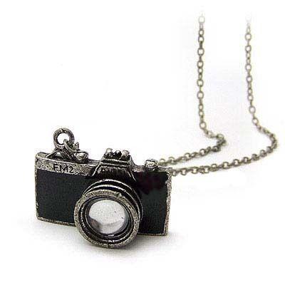 """Collier """"APPAREIL PHOTO"""" noir - Dimension du tour de cou : 69 cm  Dimension du pendentif : 3,3 cm  Pendentif appareil photo noir.  Prix de vente : 10 € TTC"""