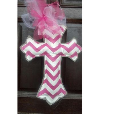 "Painted Burlap Cross Wall Hanging  Color: Hot Pink, White  Size: Cross measures approximately 23"" (25"" to top of hanger); 17"" in width  Material: Burlap, Canvas  Weather resistant (burlap painted with exterior grade paint, canvas primed with Kilz exterior, painted with acrylic paint and sealed with polyurethane. Filler is made of plastic.  Wire Hanger attached along with pink and white tulle bow. Back of cross is plain.  Handcrafted in the USA"