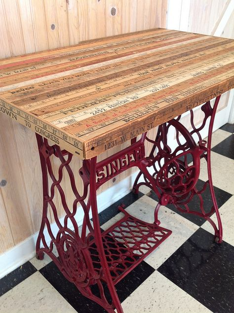 An antique Singer treadle sewing machine base finds new life as a table with the addition of vintage yardsticks nailed to an oak top.