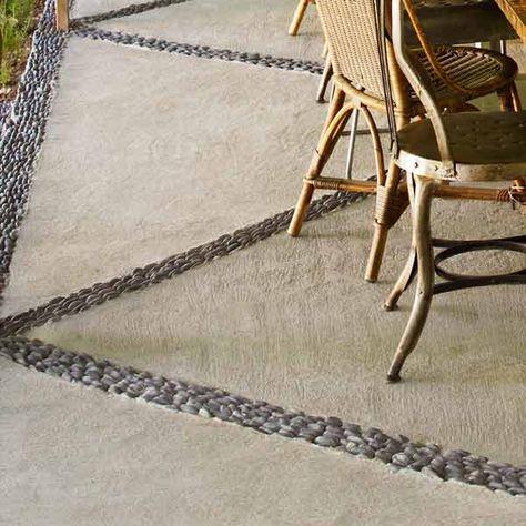 Give a plain concrete pad a graphic upgrade. Snap chalk lines to map out a design, and cut channels with a concrete saw. Fill them with wet concrete and embed river rocks, making them level with the pad.