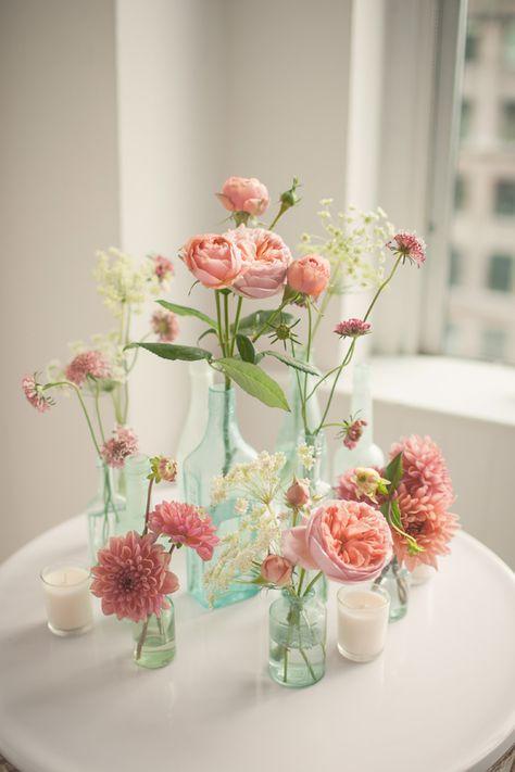 pink floral arrangements in glass bottles, photo by MGB Photo http://ruffledblog.com/manhattan-loft-wedding #centerpieces #flowers