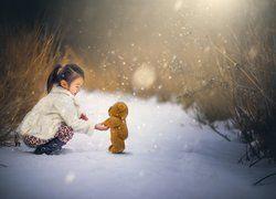 Dziewczynka z pluszowym misiem na śniegu