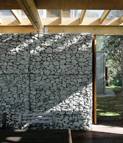 The Herbsts designed the home with a covered terrace to encourage outdoor living in the island's temperate climate (with Gabion wall)