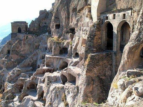Vardzia, un monasterio rocoso. Es un monasterio masculino, actualmente activo, perforado en la roca que forma la pared de una montaña sobre el río Mtkvari, en el sur de Georgia. Se trata de un gran complejo de cuevas y túneles que se remonta al siglo XII y que se extiende aproximadamente unos 500 metros a lo largo de la ladera montañosa. Posee más de 6.000 estancias distribuidas en trece pisos, así como una iglesia, un salón del trono y un sistema de riego para cultivos en terrazas.