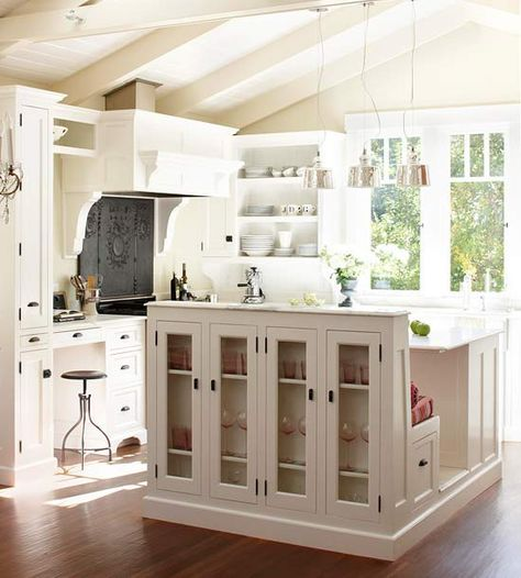 Three-In-One Kitchen Island - combines a prep station, a banquette with storage and a glass-front display cabinet. This is a brilliant space-saving idea!