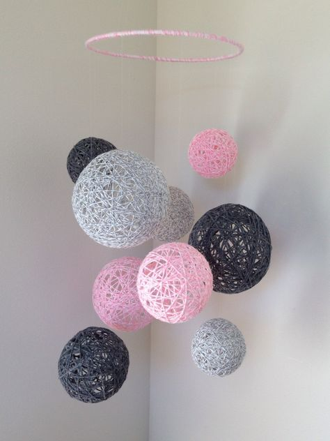A baby mobile that will catch ur babys attention and put the perfect finishing touch on your nursery! Baby pink with two shades of grey yarn balls strung from a hoop with invisible fish line. Ball sizes range from 3-1/2 inches - 6 inches and the height of mobile is approx. 24 inches from the hoop down with top string being adjustable to your preference. The perfect gift for your friends baby shower and a lovely way to dress up your own nursery before your little one arrives. Intended for deco...