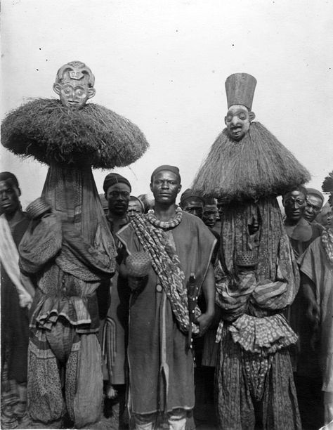 Africa | Masked dancers, standing next to Nji Wamben, a servant of the King. Cameroon. ca. 1910 - 1930 | ©Anna Wuhrmann