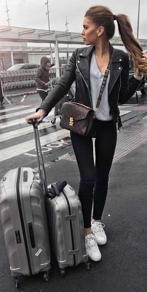 Travel Outfits Airport style: How To Look Fashionable During Travel - Just The Design Iva Nikolina Juric V neck top black jeans classic leather jacket sleek travel-ready style Sneakers essential for comfort ease when travelling! Brands not specified.
