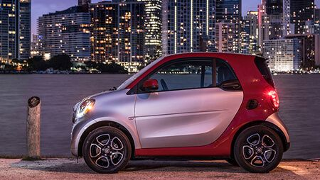 A 2018 Smart Eq Fortwo Is Parked Along A Body Of Water At Night