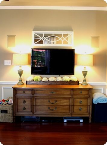 Tv mounted on wall over dresser, flanking lamps, pretty mirror overhead-- wonder if we can mount our tv