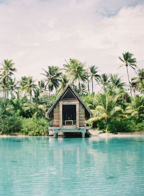 A wooden cabin floats on calm crystal clear waters surrounded by palm trees and…