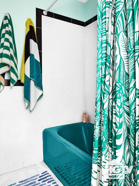 A tropical printed shower curtain, light blue walls and white hexagon tile give this bathroom major character. See more on HGTV.com.