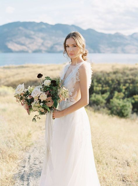 A ruffled tulle wedding dress, pastel tablescape, crystal goblets and foraged blooms? This lakeside elopement inspiration is straight out of a European fairytale. If you love classic artwork, vintage engagement rings or fine art florals, head to Ruffled Blog to see more from this ethereal gallery #lakeelopement #fineartwedding #foragedflowers