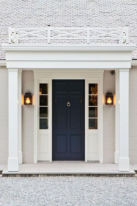 Beautiful home exterior boasts a navy front door flanked by sidelights illuminated by carriage ...