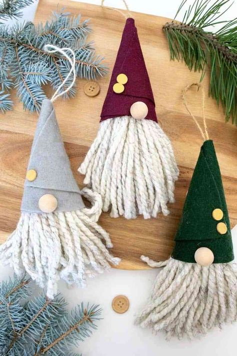 Make cute gnome ornaments from felt and yarn. Get the free printable hat template and make lots of these oversized Scandinavian gnome decorations for your Christmas tree, door knob decorations, and more. #gnomes #Christmasgnomes #nosewornaments #diyornaments