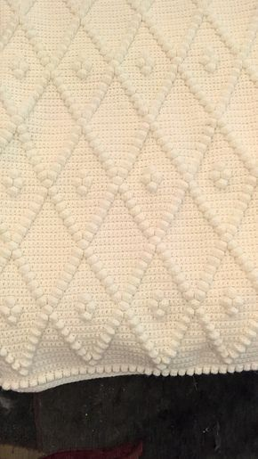This is a single crochet afghan with bobbles that is worked in one piece. The pattern is easier than it looks, and is easy to work without the pattern once the design is established. If you wish to make the pattern wider, each additional diamond in width requires 16 additional chains and adds approximately 4.5 inches. To make the pattern longer, each additional repeat adds approximately 8 inches in length.