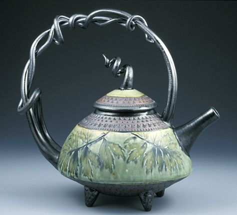 """""""Kettle Teapot""""  Ceramic Teapot    Created by Suzanne Crane  Flora from the Blue Ridge Mountains imprints this wheel-thrown stoneware teapot with twined handle and knob. Glazed in green and black with red iron oxide on the hand-stamped border. Leaf specimens vary seasonally. Each twisted handle is unique and will vary from image shown.   $625.00"""