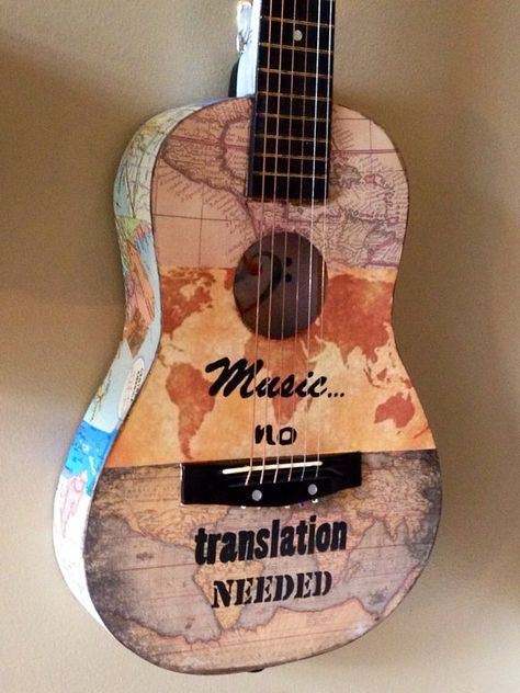 The world map mini guitar art is a celebration of music. It is collaged on all sides with vintage maps and art papers of the world and